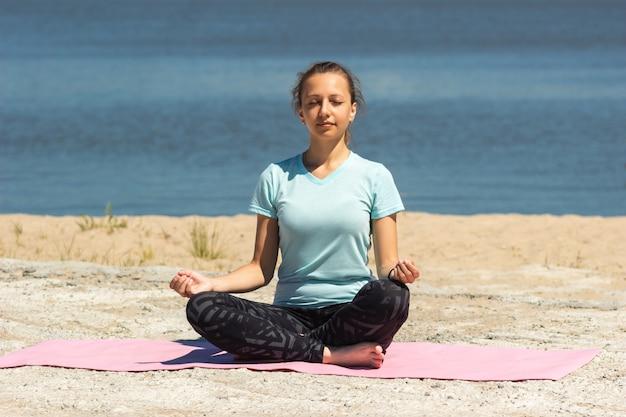 Молодая довольно внимательная женщина медитирует, держа пальцы в знаке йоги на розовом коврике у моря