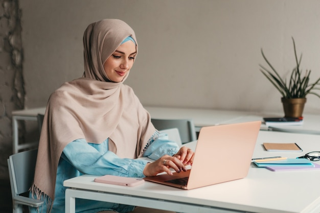 Young pretty modern muslim woman in hijab working on laptop in office room, education online