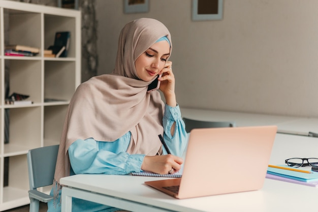 Giovane donna musulmana abbastanza moderna in hijab che lavora al computer portatile nella stanza dell'ufficio, istruzione online