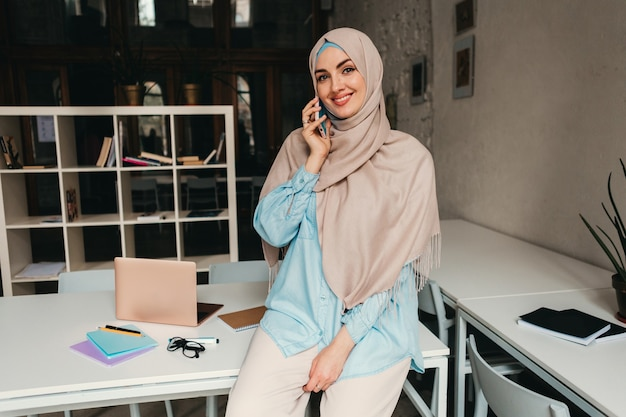 Young pretty modern muslim woman in hijab working on in office room, education online