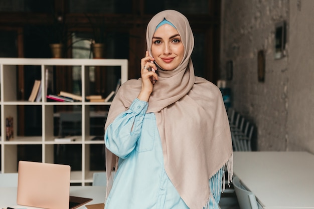 ヒジャーブを着た若いかなり現代のイスラム教徒の女性が事務室で取り組んでおり、オンラインで教育を受けている