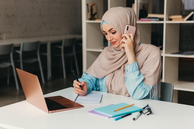 オフィス ルームでラップトップに取り組んでいるヒジャーブの若いかなり現代のイスラム教徒の女性、オンライン教育