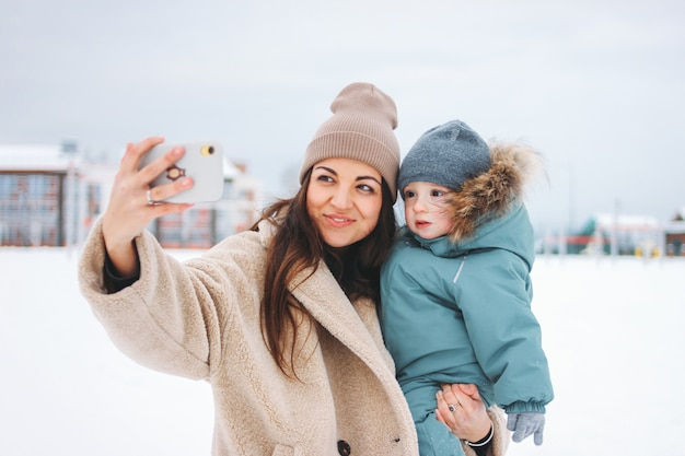 Young pretty mom brunette woman with cute baby boy in winter suit making selfie on street
