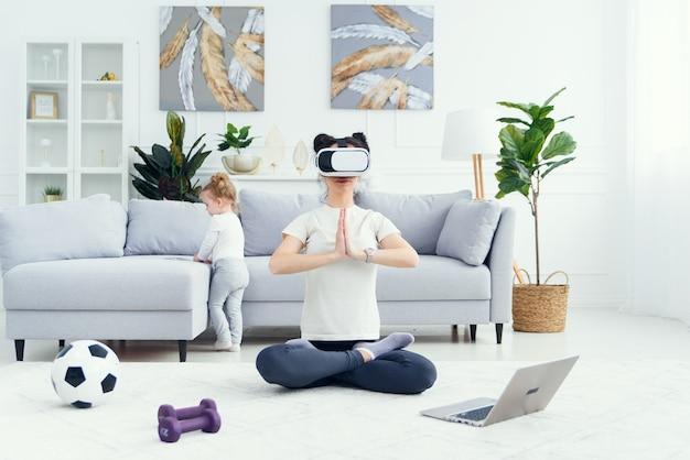 Молодая красивая мама медитирует в позе лотоса-йоги, используя очки виртуальной реальности, пока ее дочь смотрит мультфильмы дома на заднем плане.