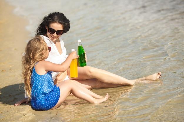 Молодая красивая мать и ее маленькая дочь на пляже, с удовольствием