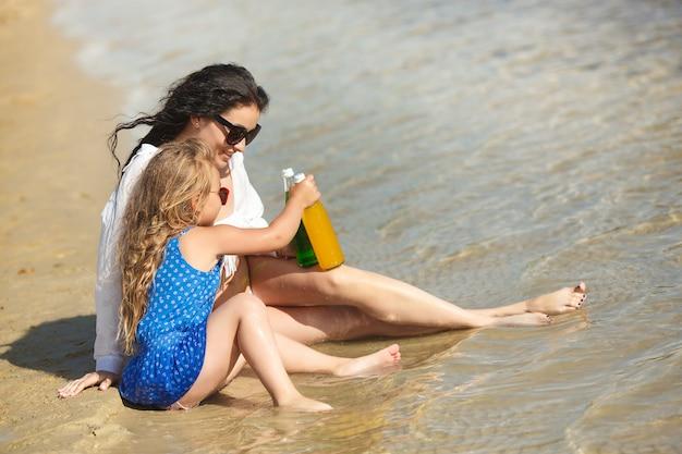 Молодая красивая мать и ее маленькая дочь на пляже, весело