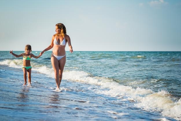 푸른 하늘에 대 한 햇살 따뜻한 여름날에 휴가 기간 동안 바다 해안에서 실행 젊은 예쁜 엄마와 딸