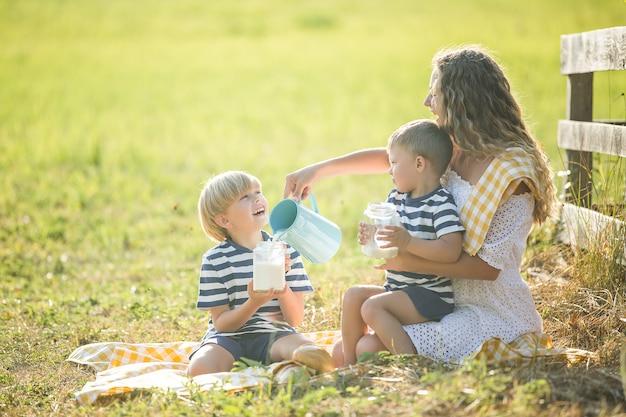 若いかわいい母親が彼女の小さな子供たちとピクニックをしています。屋外で牛乳を飲む家族