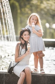 Young pretty mother and her daughter having fun together near the fountain. beautiful woman and her little child eating ice cream. cheerful family having fun.