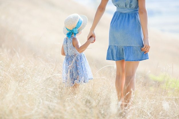 Young pretty mother and her daughter outdoors. closeup portrait of happy family on wild nature field. girls having fun.