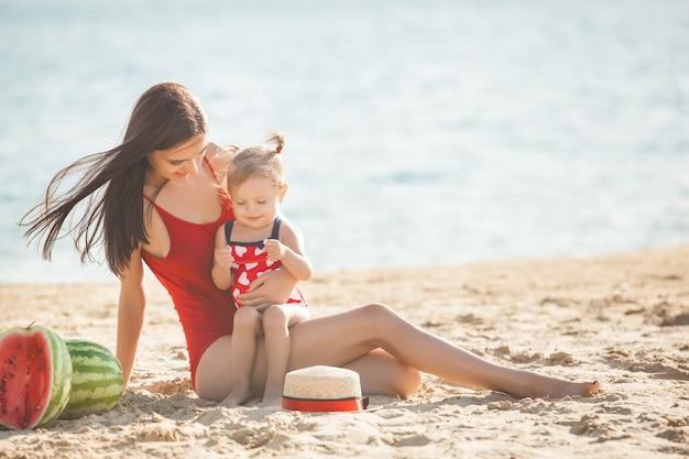 Молодая милая мать играя с ее маленькой милой дочерью на пляже. любящая мама с удовольствием с ребенком на берегу моря