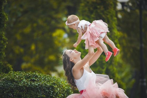 공원에서 산책 그녀의 작은 아기 딸과 함께 젊은 예쁜 어머니. 엄마와 그녀의 아이 야외. 행복한 가족.