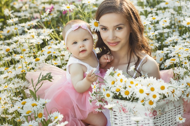 Young pretty mother with her little baby outdoors. beautiful woman with her daughter on the nature. infant child with her parent on the chamomile field