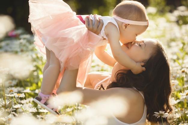若い可愛い屋外で彼女の小さな赤ちゃんと母親。自然に彼女の娘と美しい女性。カモミール畑で彼女の親と幼児