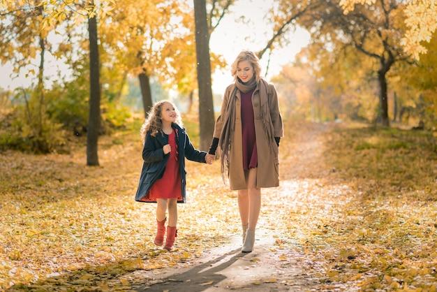 Молодая красивая мать с маленькой дочкой развлекается осенью