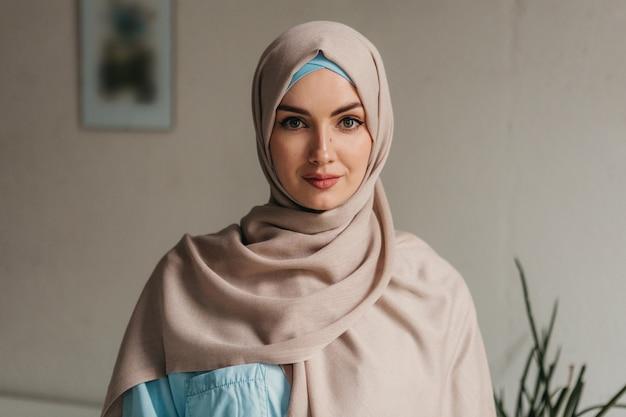 オフィス ルームでラップトップに取り組んでいるヒジャーブの若いかなりイスラム教徒の女性、オンライン教育