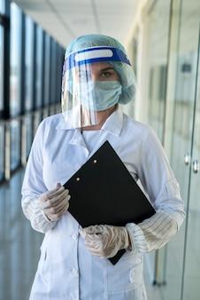 クリニックで新しい感染性ウイルスコロナウイルスcovid-19からフェイスシールドマスク保護を身に着けている制服を着た若いかわいい看護師