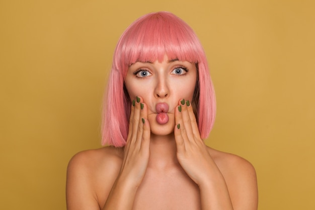 Young pretty open-eyed woman with pink bob hairstyle holding raised hands on her cheeks and making faces while standing over mustard wall