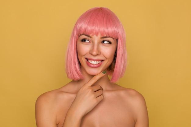 Giovane bella donna dai capelli rosa con trucco naturale che tiene il mento con la mano alzata e mostra i suoi denti bianchi perfetti mentre sorride allegramente, isolato sul muro di senape