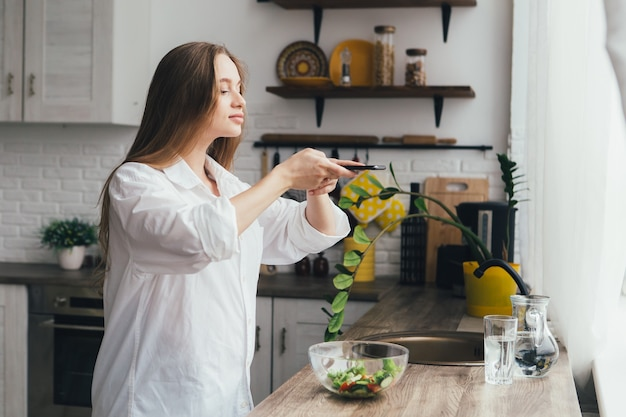 Young pretty pregnant girl takes photos of a prepared salad on her smartphone