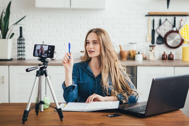 かなり妊娠中の若い女の子は、自宅で隔離モードで隔離モードで作業し、スマートフォンにビデオを記録します