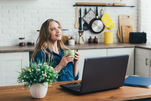 Молодая симпатичная беременная девушка работает дома в режиме самоизоляции на карантине и отдыхает с кофе