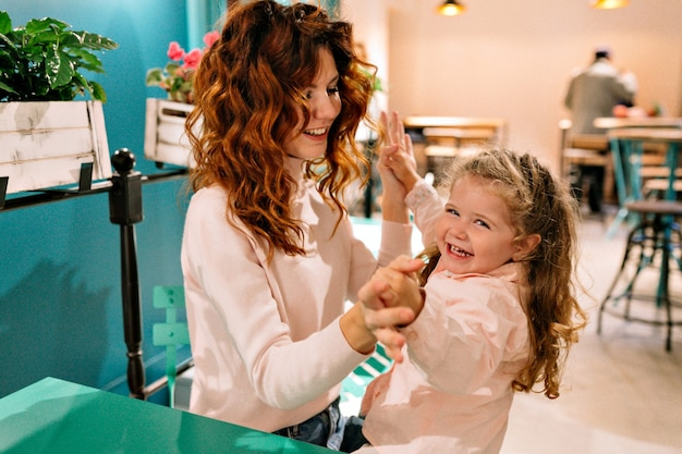 彼女の小さな愛らしい巻き毛の子供を持つ若いかなり赤い髪の母親は家族で週末を過ごします