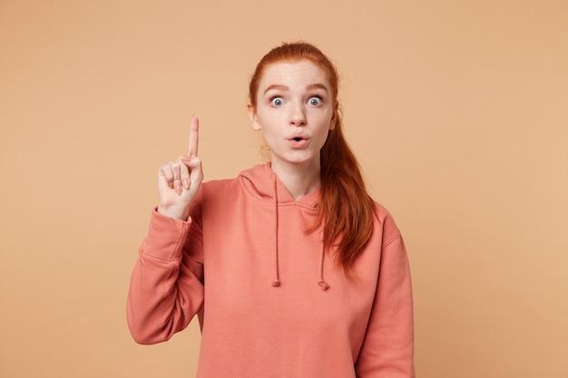 Молодая красивая рыжеволосая женщина изолирована над бежевой стеной, указывая пальцем вверх, выскакивая глаза с успешной идеей