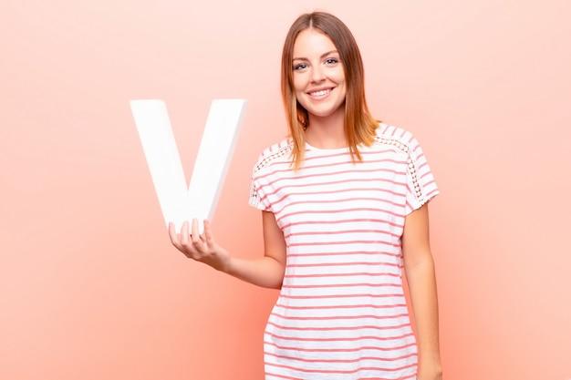 若い可愛い赤い頭の女性は興奮して、幸せで、うれしそうな、アルファベットの文字vを押して単語や文章を形成します。