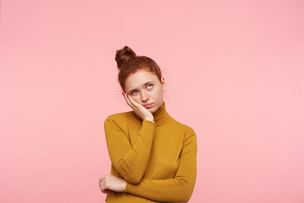 Young pretty redhead female with bun hairstyle isolated