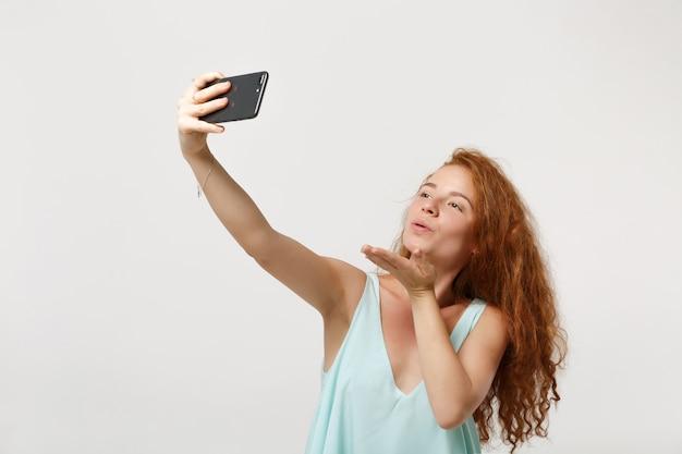 白い背景で隔離のポーズをとってカジュアルな明るい服を着た若いかわいい赤毛の女性の女の子。人々のライフスタイルの概念。コピースペースをモックアップします。携帯電話で自分撮りをして、エアキスを吹いて吹く。