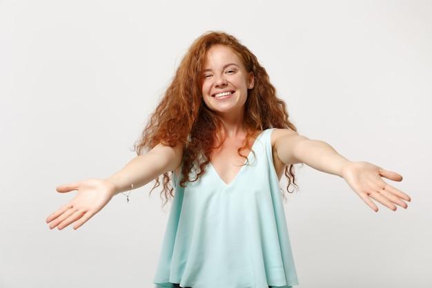 白い背景のスタジオの肖像画に分離されたポーズをとってカジュアルな明るい服を着た若いかわいい赤毛の女性。人々の誠実な感情のライフスタイルの概念。コピースペースをモックアップします。伸ばした手で立っています。