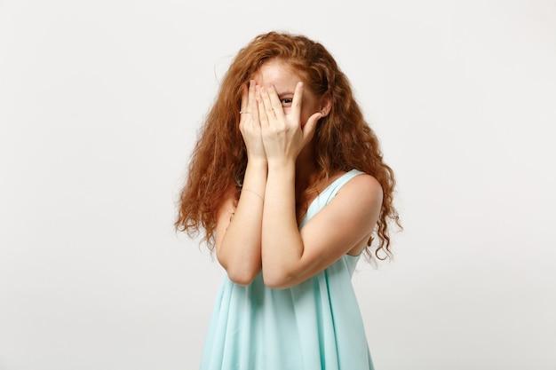 白い壁の背景に分離されたポーズをとってカジュアルな明るい服を着た若いかわいい赤毛の女性。人々の誠実な感情のライフスタイルの概念。コピースペースをモックアップします。顔を手で覆い、隠れ、のぞきます。