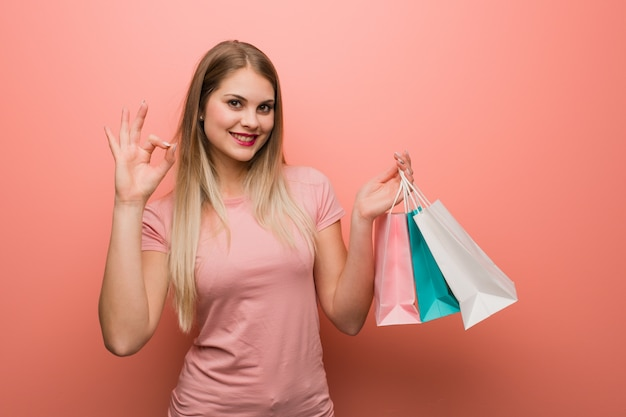 Young pretty russian girl cheerful and confident doing ok gesture. she is holding a shopping bags.