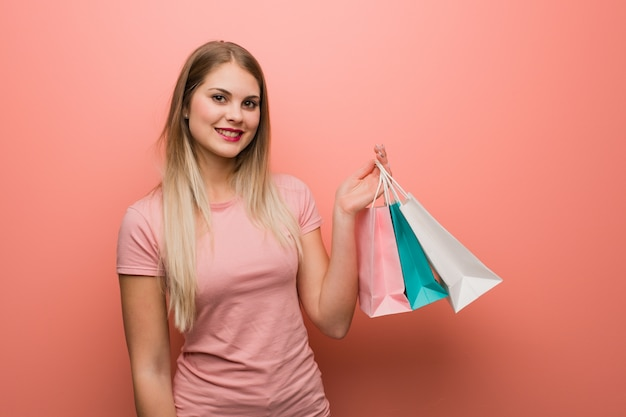 Young pretty russian girl cheerful with a big smile. she is holding a shopping bags.
