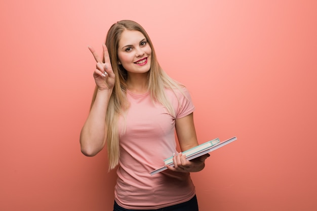 Young pretty russian girl fun and happy doing a gesture of victory. she is holding books.