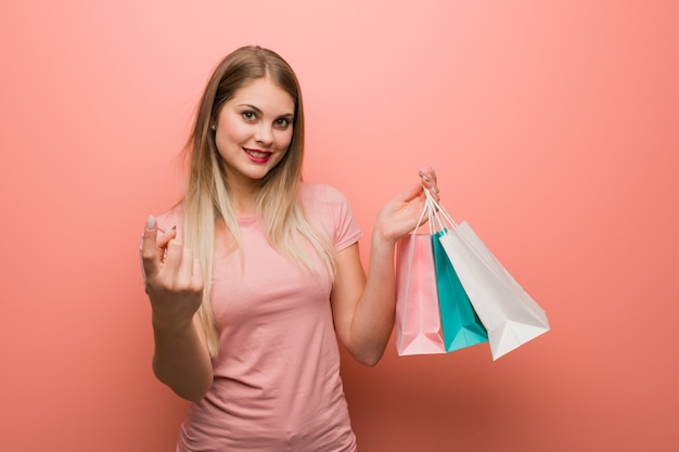 Young pretty russian girl inviting to come. she is holding a shopping bags.