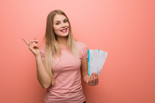 Young pretty russian girl pointing to the side with finger. she is holding tickets.