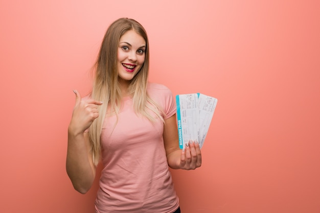 Young pretty russian girl surprised, feels successful and prosperous. she is holding an air tickets.