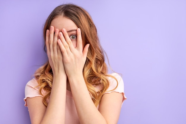 Young pretty scared woman posing isolated covering face, frightened female stand in fear
