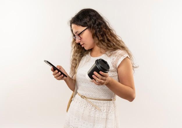 젊은 예쁜 여학생 안경을 쓰고 다시 가방을 들고 커피 컵을 들고 복사 공간이 흰색 배경에 고립 된 그녀의 전화를 사용