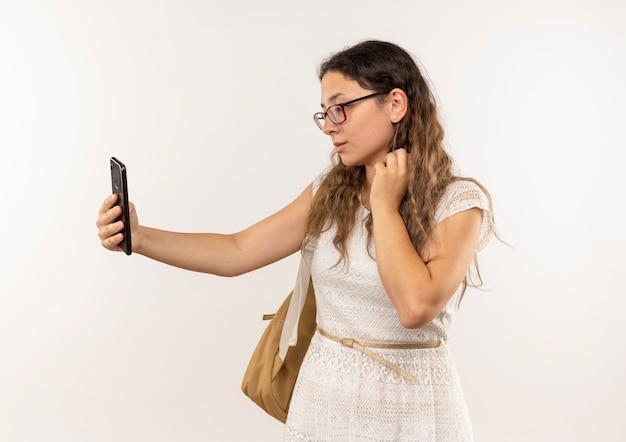 Молодая симпатичная школьница в очках и задней сумке, делающая селфи на белом фоне