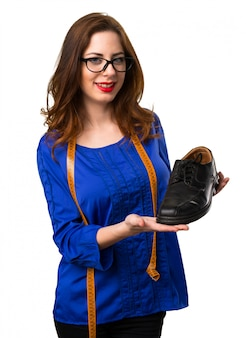 Young and pretty seamstress with tape measure and  holding a shoe