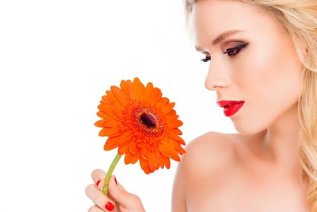 Молодая довольно чувственная блондинка держит цветок герберы