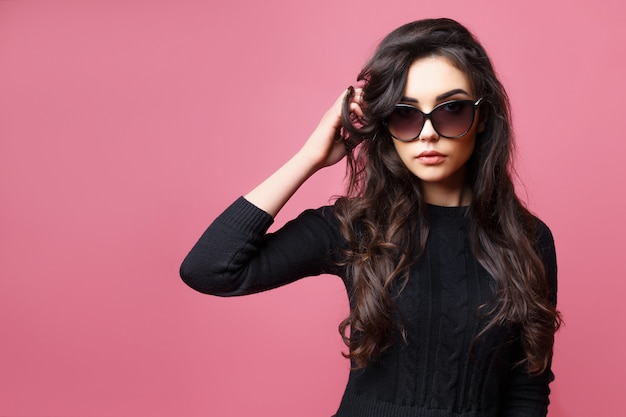 Young pretty sexy woman or woman with cute face and long brunette hair wearing sunglasses and black sweater