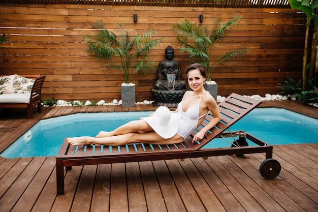 Молодая красивая стройная красивая девушка отдыхает у бассейна в купальнике с солнцезащитным кремом