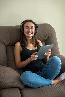 편안한 소파에 누워 그녀의 태블릿을보고 젊은 꽤 슬림 여자. 자유