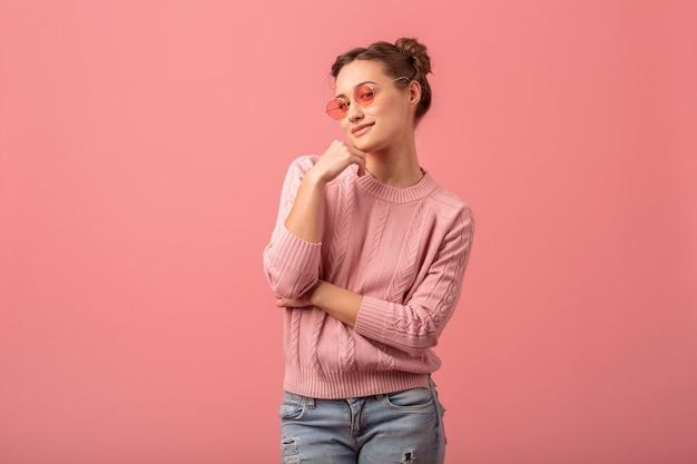 분홍색 스튜디오 배경에 고립 분홍색 스웨터와 선글라스를 착용하는 세련된 봄 옷에 젊은 꽤 웃는 아름다운 여자