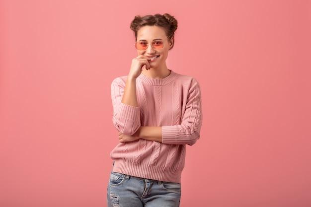 Giovane bella donna abbastanza sorridente in vestito alla moda primaverile che indossa un maglione rosa e occhiali da sole isolati su sfondo rosa studio