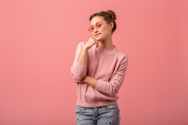 Young pretty smiling beautiful woman in stylish spring outfit wearing pink sweater and sunglasses isolated on pink studio background